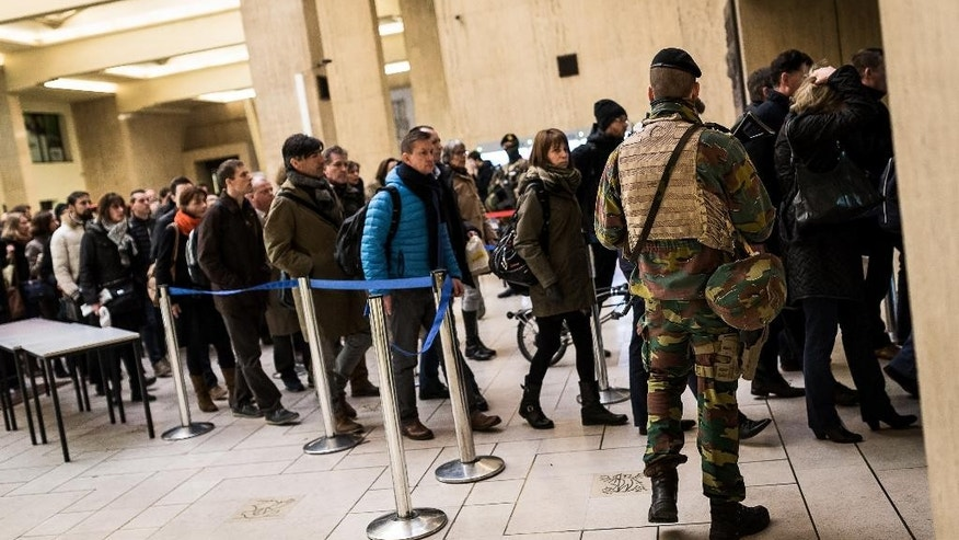 Belgian Army soldiers patrol as passengers line up to have their bags searched at the Central Station in Brussels on Wednesday, March 23, 2016. Belgian authorities were searching Wednesday for a top suspect in the country's deadliest attacks in decades, as the European Union's capital awoke under guard and with limited public transport after 34 were killed in bombings on the Brussels airport and a subway station. (AP Photo/Valentin Bianchi)