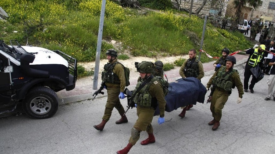 Israeli soldiers carry the body of one of two Palestinian who were killed after a stabbing attack in Hebron, West Bank, Thursday, March 24, 2016. The Israeli military has detained a soldier who was captured on video shooting an injured Palestinian lying on the ground. The army says the incident took place in the West Bank city of Hebron after two Palestinians stabbed and wounded an Israeli soldier. (AP Photo)