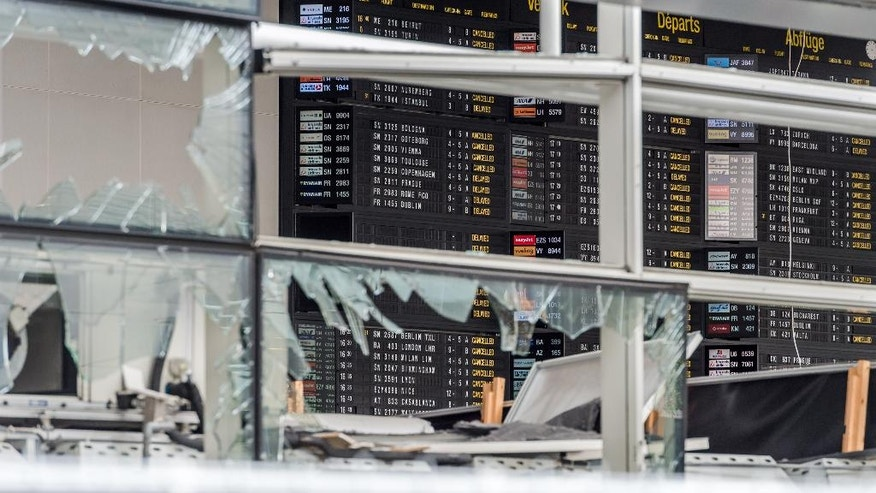 An arrivals and departure board is seen behind blown out windows at Zaventem Airport in Brussels on Wednesday, March 23, 2016. Belgian authorities were searching Wednesday for a top suspect in the country's deadliest attacks in decades, as the European Union's capital awoke under guard and with limited public transport after scores were killed and injured in bombings on the Brussels airport and a subway station. (AP Photo/Geert Vanden Wijngaert, Pool)