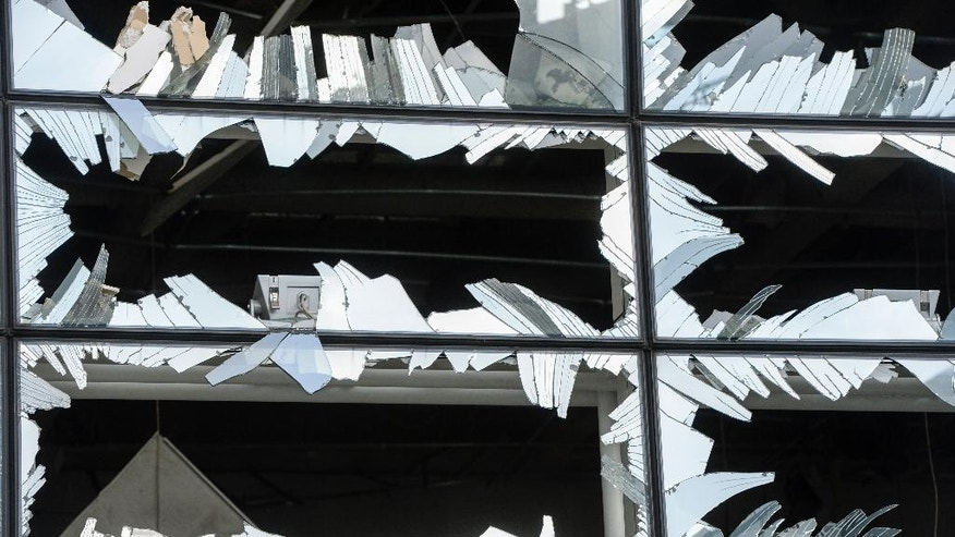 Blown out windows at Zaventem Airport terminal in Brussels on Wednesday, March 23, 2016. Belgian authorities were searching Wednesday for a top suspect in the country's deadliest attacks in decades, as the European Union's capital awoke under guard and with limited public transport after scores were killed and injured in bombings on the Brussels airport and a subway station. (AP Photo/Frederic Sierakowski, Pool)