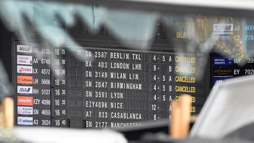 A departure and arrivals board is seen behind a blown out window at Zaventem Airport in Brussels on Wednesday, March 23, 2016. Belgian authorities were searching Wednesday for a top suspect in the country's deadliest attacks in decades, as the European Union's capital awoke under guard and with limited public transport after scores were killed and injured in bombings on the Brussels airport and a subway station. (AP Photo/Yorick Jansens, Pool photo via AP)
