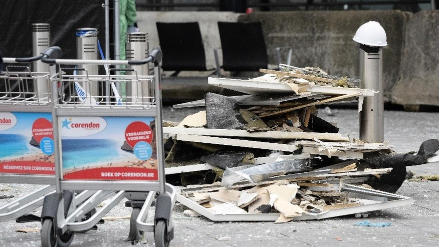 Luggage carts are parked near damage at Zaventem Airport in Brussels on Wednesday, March 23, 2016. Belgian authorities were searching Wednesday for a top suspect in the country's deadliest attacks in decades, as the European Union's capital awoke under guard and with limited public transport after scores were killed and injured in bombings on the Brussels airport and a subway station. (AP Photo/Yorick Jansens, Pool photo via AP)