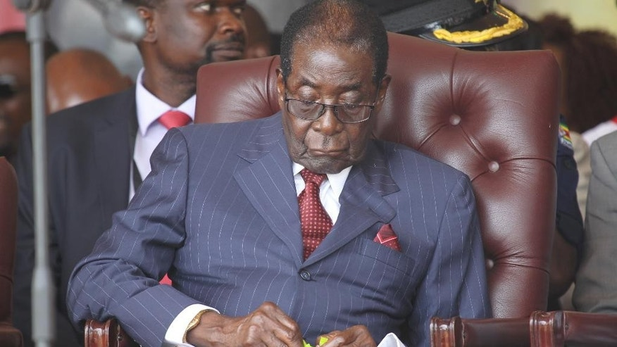 "Zimbabwean President Robert Mugabe, left,  sits with his wife Grace during commemorations to mark his 92nd Birthday celebrations in this Saturday, February, 27, 2016 photo.  Poking fun at Mugabe is a risky business which has a law that forbids ""undermining the authority of or insulting the president"".  Primary school headmaster Edson Chuwe faces a year in prison if convicted because his spoof image of Mugabe posing with singer Rihanna is not seen as funny, according to prosecutors, and a printed screen shot of the image is now a key peace of evidence in the trial against the headmaster who posted it on Facebook. (AP Photo/Tsvangirayi Mukwazhi)"
