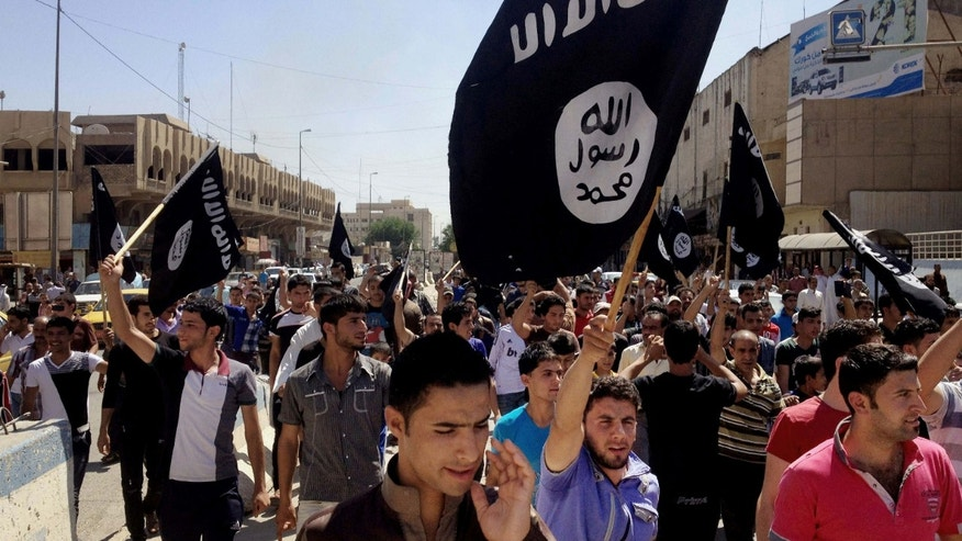 FILE - In this June 16, 2014 file photo, demonstrators chant pro-Islamic State group slogans as they carry the group's flags in front of the provincial government headquarters in Mosul, Iraq.