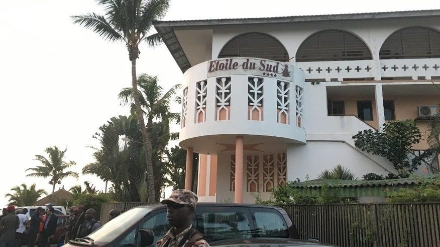 FILE- In this Sunday, March 13, 2016 file photo, a Ivory Coast soldier stands outside the Etoile du Sud, where gunmen attacked, in Grand Bassam, Ivory Coast. Ivory Coast plans to establish new centers for rapid response forces to protect soft targets throughout the country following an attack by Islamic extremists on a popular beach town earlier this month that left 19 dead, the country's prime minister said Thursday. March 24, 2016. (AP Photo/Christin Roby, File)