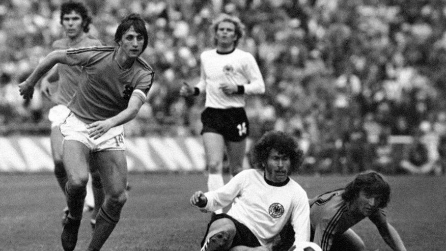 FILE - This is a July 7, 1974  file photo  of Dutch forward Johan Cruyff, left, runs past German defender Paul Breitner, sitting on the pitch  during the final of the Soccer World Cup at the Olympic Stadium in Munich, Germany. Dutch soccer great Johan Cruyff, who revolutionized the game with the concept of 'Total Football,' died Thursday March 24, 2016. He was 68. (AP Photo)