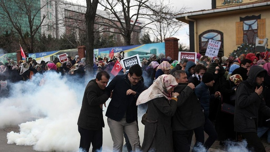 FOR STORY TURKEY MEDIA UNDER SIEGE - FILE - In this March 5, 2016 file photo, people run as riot police use tear gas and water cannons to disperse people gathered in support outside the headquarters of Zaman newspaper in Istanbul.  Turkey's most defiantly government-critical newspaper has, almost overnight, turned into a pro-government publication joining scores of other media outlets that toe the government's line, while two prominent opposition journalists go on trial in Turkey, facing life imprisonment for their reports.(AP Photo/FILE)