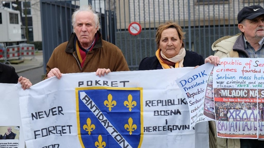Demonstrators gather outside the International Criminal Tribunal for the Former Yugoslavia before the trial of former Bosnian Serb President Radovan Karadzic, in The Hague, Netherlands, Thursday, March 24, 2016. Karadzic is blamed for a deadly campaign of sniping and shelling in the capital, Sarajevo, and the 1995 murders of 8,000 Muslim men and boys in Srebrenica. The conflict left 100,000 dead and forced more than 2 million from their homes. (AP Photo/Michael Corder)