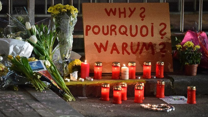 "A sign reads ""Why?"" in English, French and Flemish behind candles and flowers near the Maelbeek metro station, in Brussels on Wednesday evening, March 23, 2016. Bombs exploded Tuesday at Brussels airport and one of the city's metro stations, killing and wounding scores of people, as a European capital was again locked down amid heightened security threats. (AP Photo/Martin Meissner)"