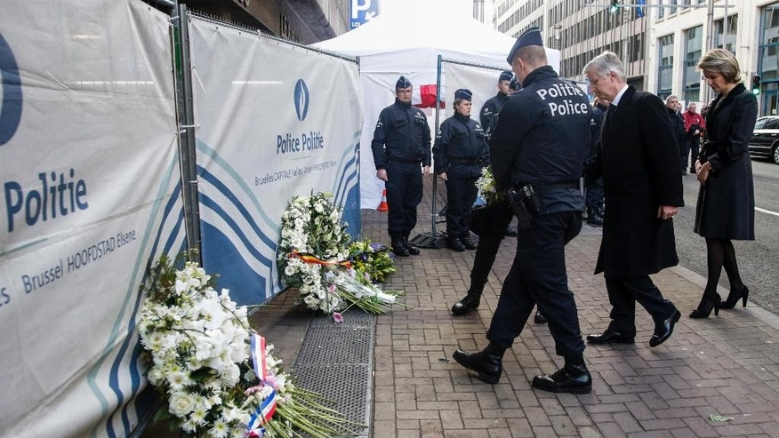 Belgium's King Philippe, center, and Belgium's Queen Mathilde, right, lay a wreath at Maelbeek metro station in Brussels on Wednesday, March 23, 2016. Belgian authorities were searching Wednesday for a top suspect in the country's deadliest attacks in decades, as the European Union's capital awoke under guard and with limited public transport after scores were killed and injured in bombings on the Brussels airport and a subway station. (Thierry Roge, Pool photo via AP)