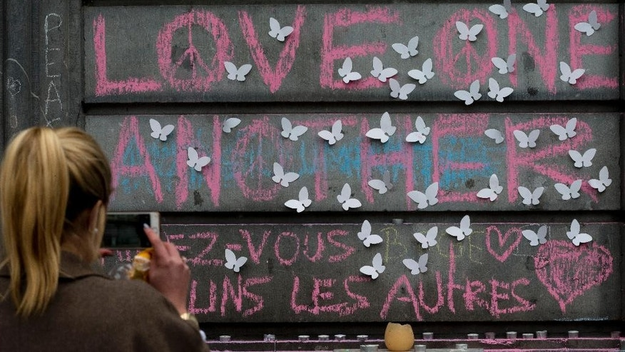 """A woman takes pictures of a wall reading """"Love One Another"""" adorned with butterflies as people mourn for the victims of the bombings at the Place de la Bourse in the center of Brussels, Belgium, Thursday, March 24, 2016. The Islamic State group has trained at least 400 fighters to target Europe in deadly waves of attacks, deploying interlocking terror cells like the ones that struck Brussels and Paris with orders to choose the time, place and method for maximum carnage. (AP Photo/Peter Dejong)"""