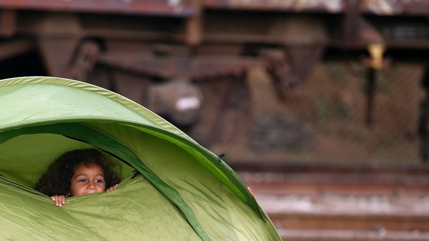 A migrant girl looks out from a tent at a train station near the make shift refugee camp at the northern Greek border point of Idomeni, Greece, Thursday, March 24, 2016. Conditions in Idomeni, where thousands have been stranded since the border shut to refugees earlier this month, have steadily deteriorated, exacerbated by days of rain that have turned the fields into muddy swamps. (AP Photo/Darko Vojinovic)
