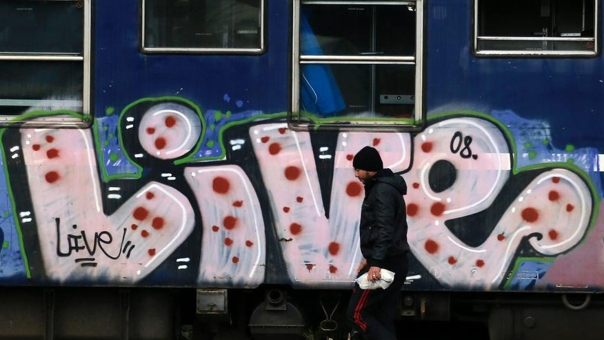 A migrant passes by a rail car at a train station near a makeshift refugee camp at the northern Greek border point of Idomeni, Greece, Thursday, March 24, 2016. Conditions in Idomeni, where thousands have been stranded since the border closed to refugees earlier this month, have steadily deteriorated, exacerbated by days of rain that have turned the fields into muddy swamps. (AP Photo/Darko Vojinovic)