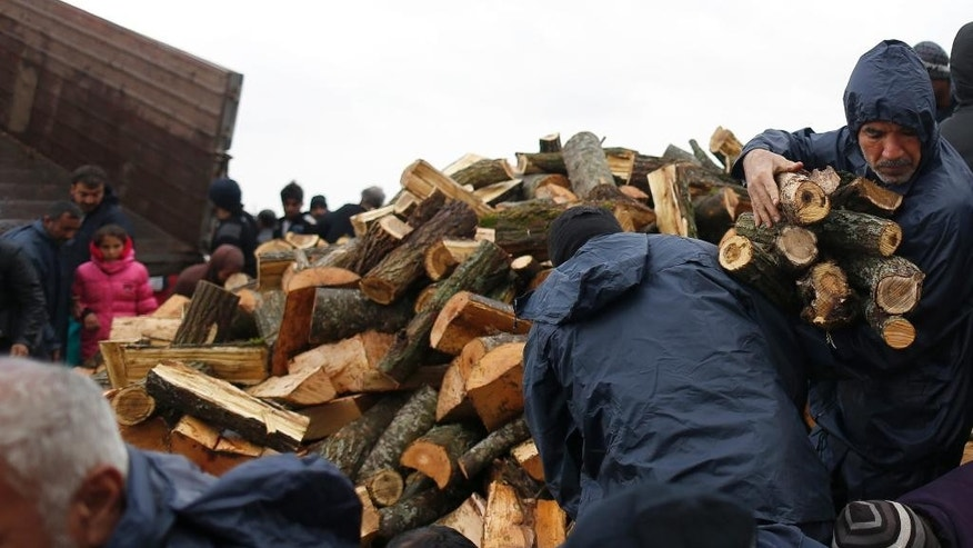Migrants mob a truck bringing donated firewood in the make shift refugee camp at the northern Greek border point of Idomeni, Greece, Wednesday, March 23, 2016. The U.N. refugee agency pulled out staff Tuesday from facilities on Lesbos and other Greek islands being used to detain refugees and migrants as an international deal with Turkey came under further strain. (AP Photo/Darko Vojinovic)