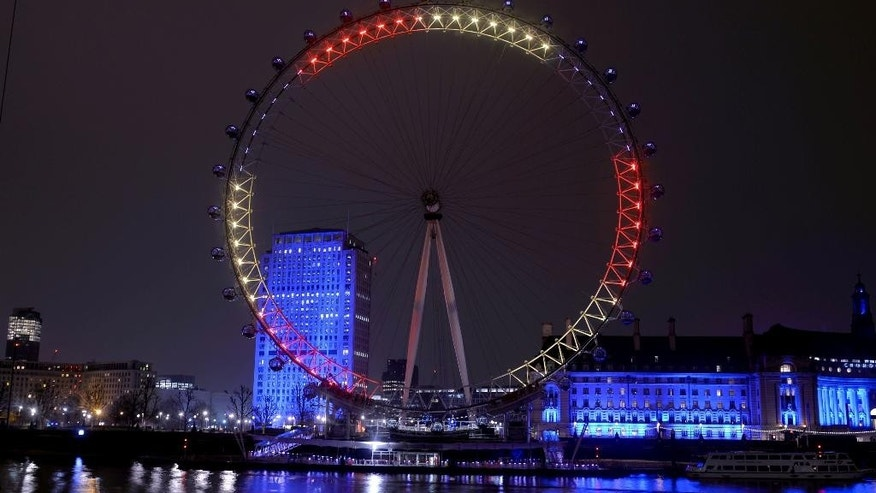 The London Eye on the banks of the River Thames is lit in the colours of the Belgian flag Wednesday March 23, 2016, as a tribute following Tuesday's terrorist attacks in Brussels. Other well know London landmarks were also lit in the same colours. (Anthony Devlin/PA via AP)  UNITED KINGDOM OUT