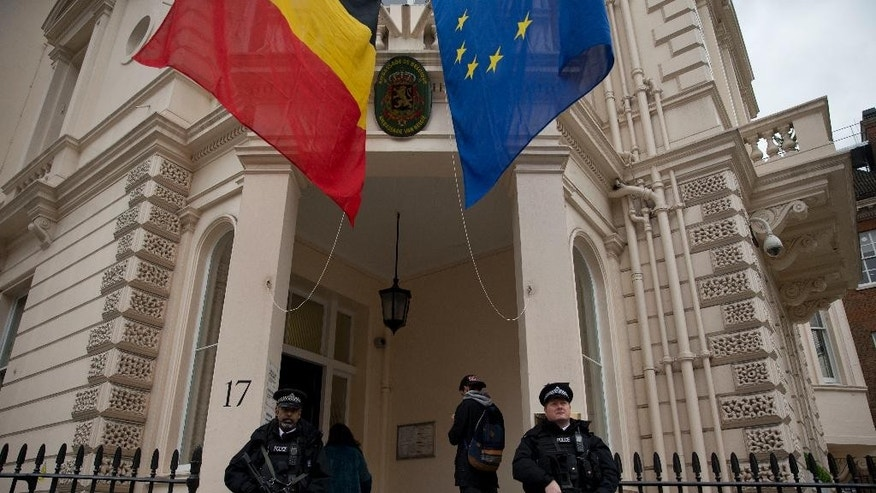 Armed British police stand guard outside the Belgian Embassy in London, Wednesday, March 23, 2016. Belgian authorities searched Wednesday for a man pictured at the Brussels airport with two apparent suicide bombers, amid growing suggestions that the bombings of the Brussels airport and subway were the work of the same Islamic State cell that attacked Paris last year. (AP Photo/Matt Dunham)