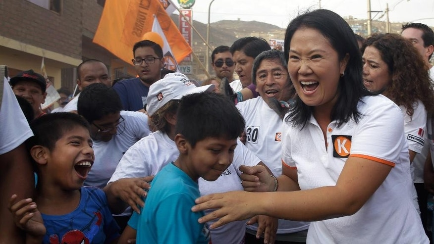 "Presidential candidate Keiko Fujimori, right, of the ""Fuerza Popular"" political party, greets supporters as she campaigns in San Juan de Lurigancho shantytown on the outskirts of Lima, Peru, Tuesday, March 22, 2016. Keiko, the daughter of former President Alberto Fujimori, is running for president in Peru's April 10 election. (AP Photo/Martin Mejia)"