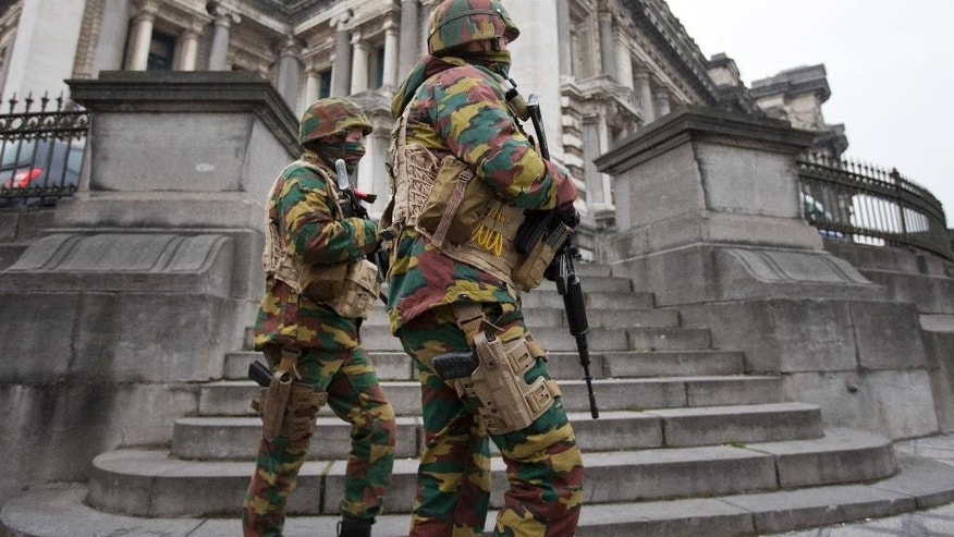 Belgium soldiers patrol around the main court building where Salah Abdeslam, the top suspect in last year's deadly Paris attacks, was expected to appear before a judge in Brussels, Belgium, Thursday, March 24, 2016. The Islamic State group has trained at least 400 fighters to target Europe in deadly waves of attacks, deploying interlocking terror cells like the ones that struck Brussels and Paris with orders to choose the time, place and method for maximum carnage. (AP Photo/Peter Dejong)