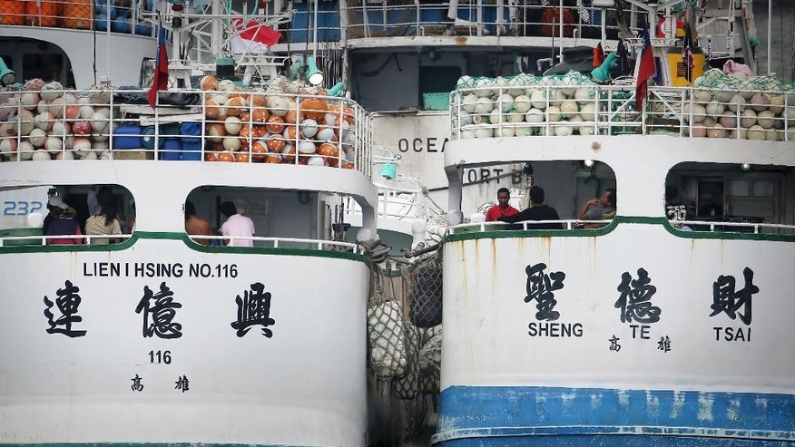 People wait on board two tuna longliners, Lien I Hsing No. 116 and Sheng Te Tsai, whose home port is in southern Taiwan, docked at the Jurong Fishery Port in Singapore Thursday, March 24, 2016. Taiwan has demanded an explanation from Indonesia after the two Taiwanese fishing boats were allegedly fired on by an Indonesian government vessel near the Strait of Malacca. (AP Photo/Wong Maye-E)