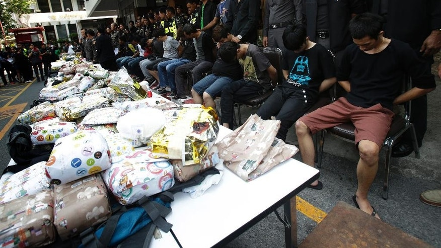 Thai police stand with suspects in front of 226 kilograms (498 pounds) of crystal meth and 8 kilograms (18 pounds) of heroin during a press conference in Bangkok, Thailand, Thursday, March 24, 2016. Thai police arrested 15 Malaysians trying to smuggle millions of dollars of crystal meth and heroin stashed in luggage on a train bound for Malaysia.(AP Photo/Sakchai Lalit)
