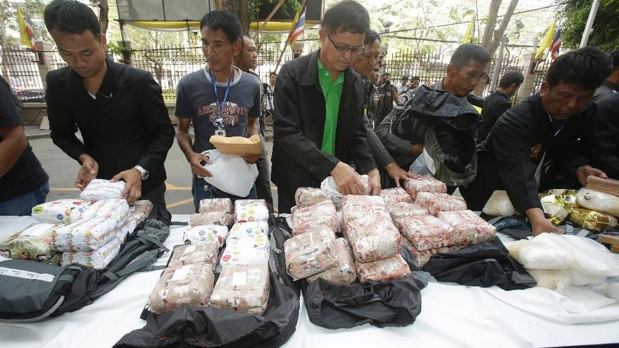 Thai policemen display some of 226 kilograms (498 pounds) of crystal meth and 8 kilograms (18 pounds) of heroin during press a conference in Bangkok, Thailand, Thursday, March 24, 2016. Thai police arrested 15 Malaysians trying to smuggle millions of dollars of crystal meth and heroin stashed in luggage on a train bound for Malaysia. (AP Photo/Sakchai Lalit)