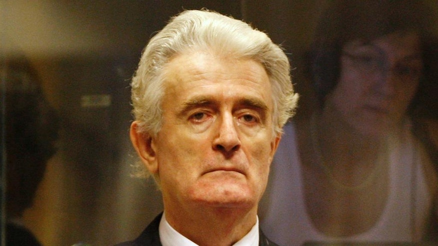 FILE - In this Thursday July 31, 2008 file photo, former Bosnian Serb leader Radovan Karadzic stands in the courtroom during his initial appearance at the U.N.'s Yugoslav war crimes tribunal in The Hague, Netherlands. More than 20 years after Bosnia's war, Radovan Karadzic will learn his fate on Thursday when U.N. judges deliver verdicts in his genocide and war crimes trial. (Jerry Lampen/Pool via AP, File)