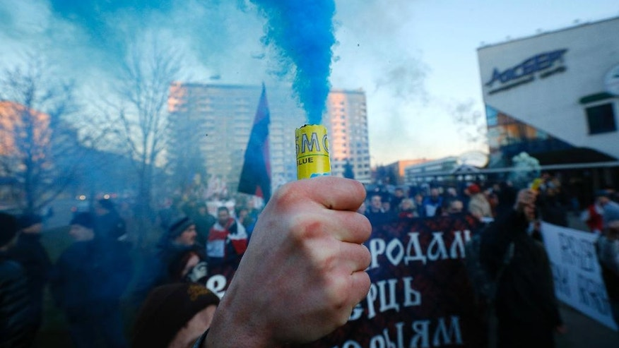 A Belarusian opposition protester holds a lighted flare during a rally in Minsk, Belarus, Friday, March 25, 2016. March 25 has long been a traditional day of demonstration for the opposition, marking what they call Freedom Day, the anniversary of the 1918 declaration of the first, short-lived independent Belarusian state. (AP Photo/Sergei Grits)