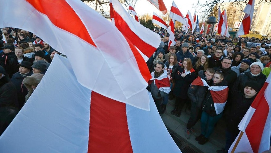 Belarusian opposition protesters wave opposition flags during a rally in Minsk, Belarus, Friday, March 25, 2016. March 25 has long been a traditional day of demonstration for the opposition, marking what they call Freedom Day, the anniversary of the 1918 declaration of the first, short-lived independent Belarusian state. (AP Photo/Sergei Grits)