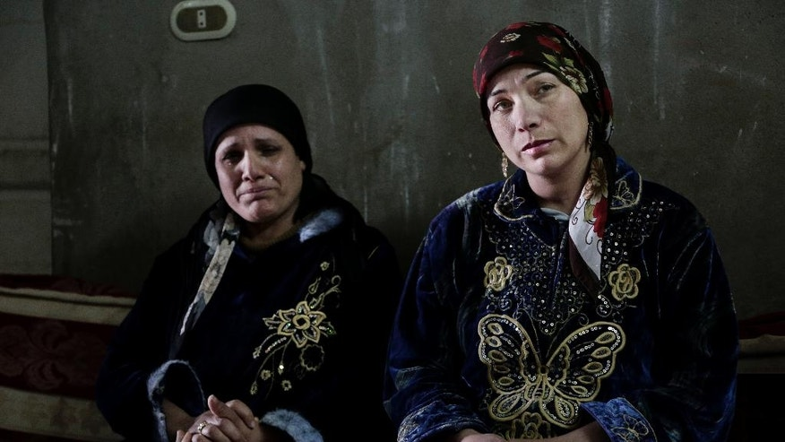 In this Thursday, March 3, 2016 photo, Fadya Shehata Moussa, left, and Iman Shaker Hanna, mothers of two of four Coptic Christian teens convicted for contempt of Islam, sit in the house of one of the teens in Bani Mazar, Minya province, Egypt. The teen boys were playing around, satirizing the extremist group, and their school supervisor just happened to be videoing them as they were imitating Muslim prayers and beheadings of the Islamic State group, their defenders say. The result has been catastrophic: The boys were sentenced to prison under Egypt's blasphemy laws. (AP Photo/Thomas Hartwell)