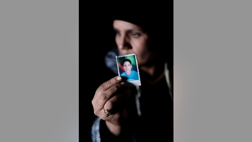In this Thursday, March 3, 2016 photo, Fadya Shehata Moussa, the mother of 17-year-old Bassem Amgad Hanna, one of four Coptic Christian teens convicted for contempt of Islam, holds a picture of her son in Bani Mazar, Minya province, Egypt. The four teens and their supervisor, who was forced to leave the village with his family, were all convicted. Though all the defendants are under 18, three were sentenced to adult prison for five years and one to a juvenile detention facility for three years. The supervisor received a three year prison sentence. (AP Photo/Thomas Hartwell)