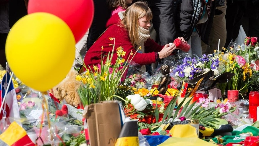A woman lights a candle at floral tributes at a memorial site at the Place de la Bourse in Brussels, Saturday, March 26, 2016. Brussels airport officials say flights won't resume before Tuesday as they assess the damage caused by twin explosions in the terminal earlier this week. (AP Photo/Geert Vanden Wijngaert)