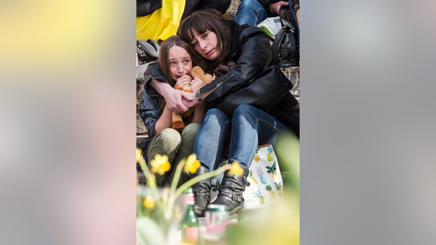 A woman embraces a girl as they observe a memorial site at the Place de la Bourse in Brussels, Saturday, March 26, 2016. Brussels airport officials say flights won't resume before Tuesday as they assess the damage caused by twin explosions in the terminal earlier this week. (AP Photo/Geert Vanden Wijngaert)
