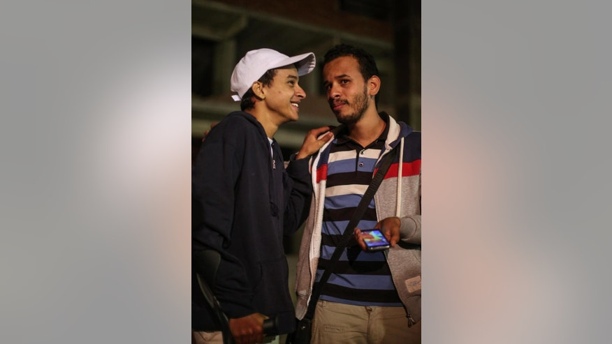 In this Thursday, March 24, 2016 photo, Egyptian activist Mahmoud Mohammed Ahmed, left, smiles next to his brother Tito Tarek, right, after his release from a police station in Cairo, Egypt. An Egyptian court on Thursday, March 24, 2016 ordered the release of Ahmed, who was accused by police of taking part in unauthorized demonstrations, possession of explosives and paying money to others to take part in street protests, his brother and lawyer told The Associated Press. He was never formally charged during his two years in detention. (AP Photo/Mohamed el Raai)