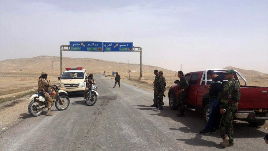 In this photo released by the Syrian official news agency SANA, Syrian government soldiers gather at the entrance of Palmyra, central Syria, Thursday, March 24, 2016. Syrian government forces pushed into the ancient town of Palmyra, where Islamic State militants appeared on the verge of collapse Thursday, while in Iraq, a military spokesman announced the start of a long-awaited operation to recapture the IS-held northern city of Mosul. (SANA via AP)