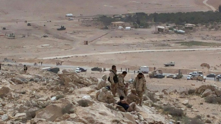 In this photo released by the Syrian official news agency SANA, Syrian government soldiers gather on a hill at the entrance of Palmyra, central Syria, Thursday, March 24, 2016. Syrian government forces pushed into the ancient town of Palmyra, where Islamic State militants appeared on the verge of collapse Thursday, while in Iraq, a military spokesman announced the start of a long-awaited operation to recapture the IS-held northern city of Mosul. (SANA via AP)