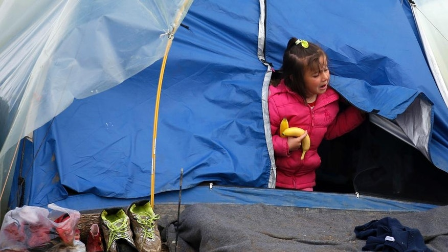 A migrant girl exits a tent in a makeshift refugee camp at the northern Greek border point of Idomeni, Greece, Friday, March 25, 2016. Some 12,000 people remain at the border camp near the village of Idomeni, most living in squalid conditions. (AP Photo/Darko Vojinovic)