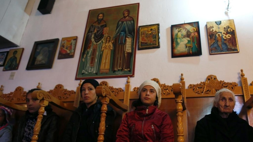 Catholic Syrian refugees attend a service with a local woman, right, in the Greek Orthodox church in the village of Idomeni, Greece, Friday, March 25, 2016. Some 12,000 people remain at the border camp near the village of Idomeni, most living in squalid conditions. (AP Photo/Darko Vojinovic)