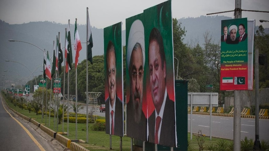 The hoardings of visiting Iranian President Hassan Rouhani, center, is on display with Pakistan's Prime Minister Nawaz Sharif, right, and President Mamnoon Hussain at the Constitution Avenue in Islamabad, Pakistan, Friday, March 25, 2016. Rouhani was expected in Pakistan on Friday in a landmark visit, his first since becoming president, at a time when Saudi Arabia is courting Islamabad to increase participation in a new Saudi-led military alliance of mostly Sunni nations, a coalition perceived by Tehran as an anti-Shiite block. (AP Photo/B.K. Bangash)