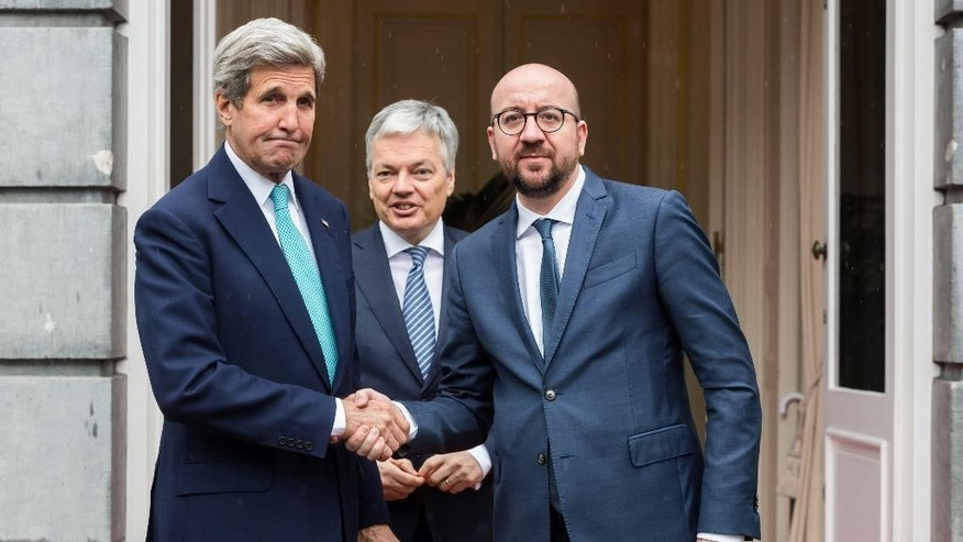 Belgium's Prime Minister Charles Michel, right, and Foreign Minister Didier Reynders, center, welcome U.S. Secretary of State John Kerry upon his arrival at the Prime Minister's residence in Brussels, Belgium, Friday, March 25, 2016. Kerry is in Brussels to pay respect to victims of terrorist attacks that left a number dead earlier this week. (AP Photo/Geert Vanden Wijngaert)