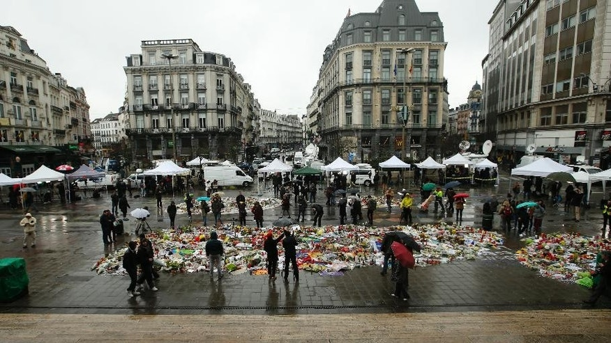 "A general view showing one of the memorial sites for the victims of the recent attacks in Brussels, and the media surrounding the area at the Place de la Bourse in Brussels, Friday, March, 25, 2016. Amid signs that life in Brussels was returning to some sort of normality on the third day of mourning the dead, authorities lowered Belgium's terror-threat level by one notch. However, they said the situation remained grave and another attack is ""likely and possible."" Belgium had been on its highest alert since Tuesday's bombings. (AP Photo/Alastair Grant)"