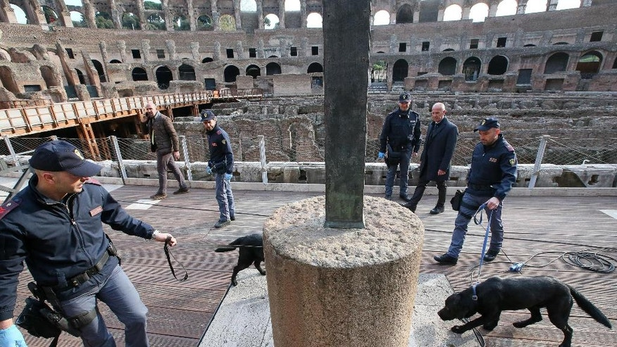 Italian Policemen with bomb sniffing dogs patrol inside the Colosseum prior to the start of the Via Crucis (Way of the Cross) torchlight procession on Good Friday in Rome, Friday, March 25, 2016. (Alessandro Di Meo/ANSA via AP Photo) ITALY OUT