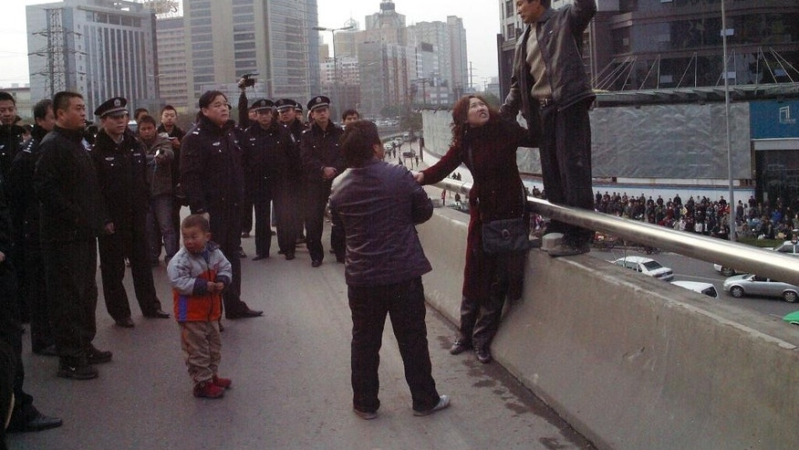 In this Dec. 8, 2006 photo, Pu Zhengxing, right, a carpenter trying to get back his unpaid wage of 3,000 yuan, takes hostage the wife of his foreman in Xi'an of China's Shaanxi province. Policemen eventually saved the hostage and arrested Pu. Wage arrears are a major problem for Chinese laborers, especially migrants working on casual terms in the construction industry. (Color China Photo via AP) CHINA OUT