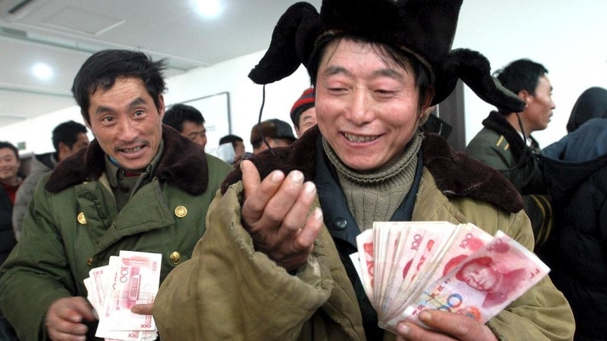 FILE - In this Dec. 29, 2006, file photo, Chinese migrant worker Zhang Guijun, foreground, reacts as he receives his delayed wages of 6,960 yuan in Shenyang, northern China's Liaoning province.  Wage arrears are a major problem for Chinese laborers, especially migrants working on casual terms in the construction industry. Wages are supposed to be paid up before workers travel home for last month's Lunar New Year holiday, but many contractors still fail to pay up.  (EyePress via AP, File) CHINA OUT