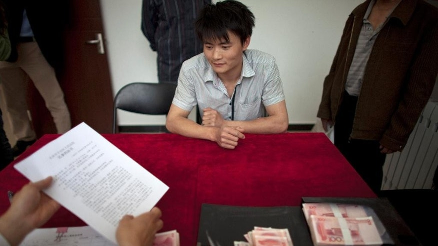 FILE- In this May 19, 2011, file photo, a lawyer, front, hands over legal documents to a migrant worker, center in the back, whose delayed wages were claimed through lawsuits with free legal aid at Beijing Zhicheng Migrant Workers' Legal Aid and Research Center in Beijing, China. Wage arrears are a major problem for Chinese laborers, especially migrants working on casual terms in the construction industry. Wages are supposed to be paid up before workers travel home for last month's Lunar New Year holiday, but many contractors still fail to do so. (AP Photo/Alexander F. Yuan, File)