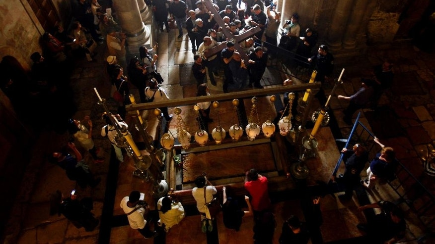 Christian faithful carry a cross into the Church of the Holy Sepulchre in Jerusalem, Friday, March 25, 2016. Catholics and Protestants commemorated the crucifixion of Jesus Christ by following the path in Jerusalem's Old City where, according to tradition, he walked on the way to the cross. (AP Photo/Mahmoud Illean)