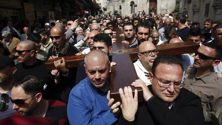 Christian faithful carry a cross during Good Friday in Jerusalem, Friday, March 25, 2016. Catholics and Protestants commemorated the crucifixion of Jesus Christ by following the path in Jerusalem's Old City where, according to tradition, he walked on the way to the cross. (AP Photo/Mahmoud Illean)