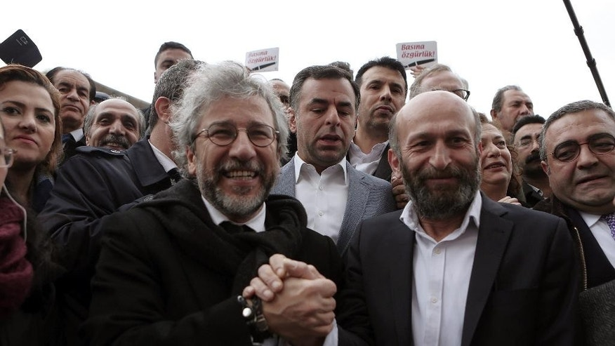 Can Dundar, the editor-in-chief of opposition newspaper Cumhuriyet, left, and Erdem Gul, the paper's Ankara representative, speak to the media before the start of their trial in Istanbul, Friday, March 25, 2016. A group of writers, including Nobel laureates, are calling on Turkey to drop charges against two prominent journalists who face life imprisonment for their reports, and to end its crackdown on free expression. Dundar and Erdem Gul, go on trial on Friday accused of espionage and other charges for their reports on alleged government arms smuggling to Syrian rebels. (AP Photo)