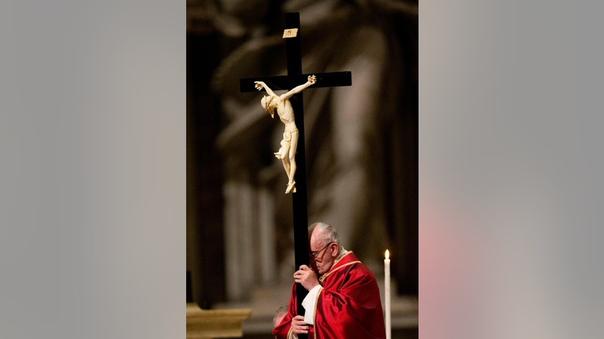 Pope Francis holds the cross during the celebration of the Lord's Passion, in St. Peter's Basilica at the Vatican Friday, March 25, 2016. (AP Photo/Alessandra Tarantino)