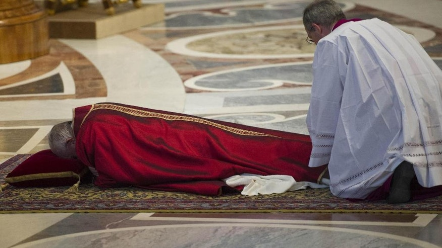 Pope Francis lies on the floor during a mass to celebrate the Lord's Passion, in St. Peter's Basilica at the Vatican Friday, March 25, 2016. (Giorgio Onorati/ANSA pool via AP Photo)