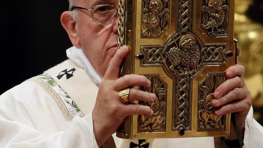 Pope Francis holds the book of the Gospels as he celebrates an Easter vigil service, in St. Peter's Basilica, at the Vatican, Saturday, March 26, 2016. (AP Photo/Gregorio Borgia)